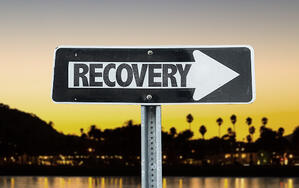 Recovery direction sign with sunset background